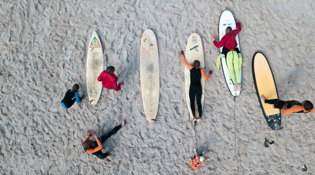 En volontär lär sydafrikanska barn och ungdomar att paddla och surfa.